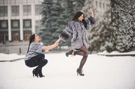winter weather: funny girls enjoying winter weather  - with film effect with small grain