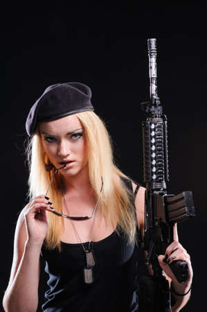girl with black hair: Beautiful army girl with gun isolated over black background Stock Photo