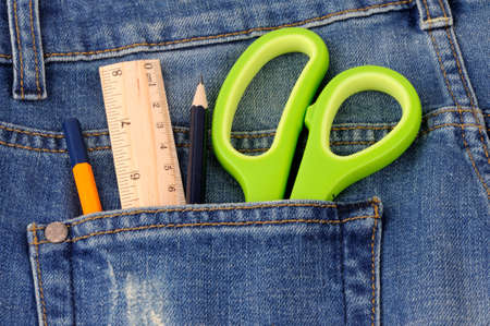 Scissors ruler  and pencil in  the blue jeans back pocket photo