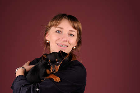 burgundy background: woman with dog on the hands over burgundy background Stock Photo