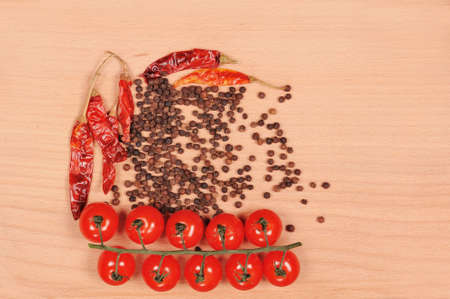 Black pepper red pepper and tomato  on the wooden cutting board