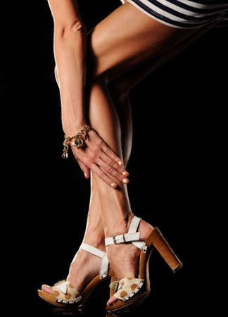 Elegant woman legs in the shoes on black background