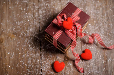 Books wrapped with color ribbon, red hearts adn snow on wooden table Stockfoto