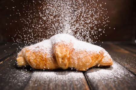 croissant with powdered sugar on wooden desk Stock Photo