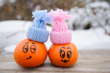 funny facial expressions on the tangerines in hats Stock Photo