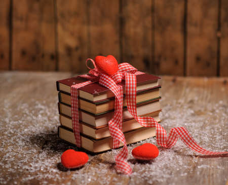 Books wrapped with color ribbon, red hearts adn snow on wooden table Foto de archivo