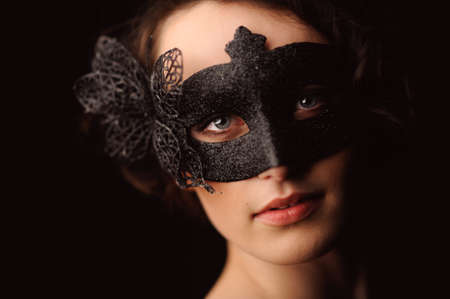 Beauty model woman wearing venetian masquerade carnival mask at party isolated on black background. Christmas and New Year celebration.