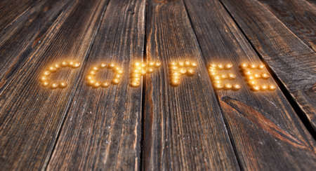 word coffee made from coffee beans on wooden background