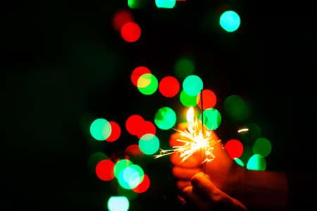 christmas sparklers over dark background with green, red, blue lights Standard-Bild