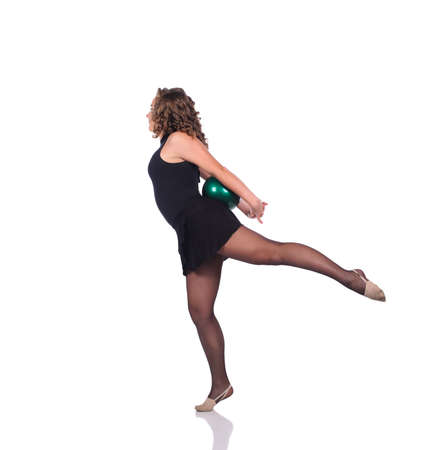 Young beautiful dancer gymnastics posing in studio with ball over white background