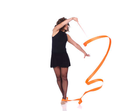 Young beautiful dancer gymnastics posing in studio with color ribbon over white background