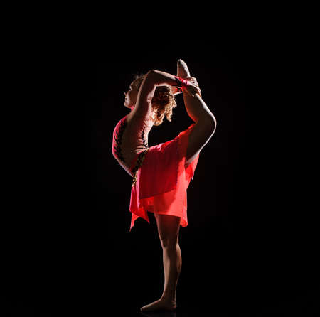 Young beautiful dancer gymnastics jumping in studio over black background Stock Photo