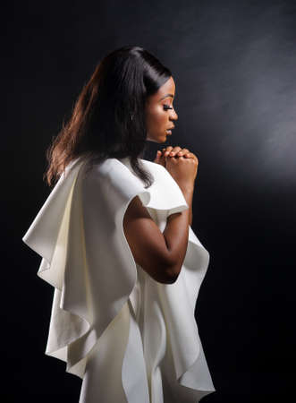 Portrait of a beautiful young African woman in white dress over black background. Studio picture