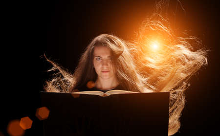 Magic Woman reading a book. black background