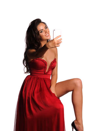 gorgeous woman in red dress making a selfie. Studio picture, grey background