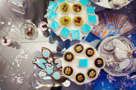 Sweet table. A plates of cakes and muffins, sweets, candys. Dessert table for a party goodies. Close up. Party reception, decorated in restaurant. Candy bar