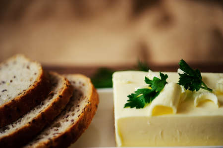 piece of butter with knife, bread and parsley on a wooden desk