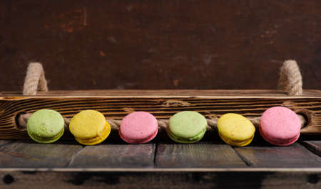 Sweet and colourful french macaroons or macaron on the wooden background