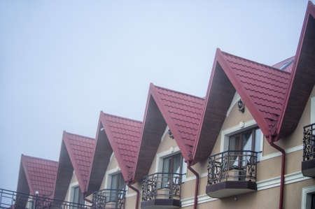 red metal tiles roof over the cloud foggy sky Stok Fotoğraf