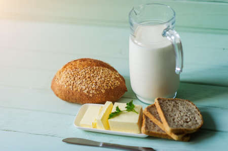 traditional bread loaf with jug of milk on a lime wooden board