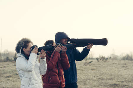 Funny picture! Photographers with cameras and tripod making outdoor landscape picture
