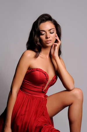 gorgeous woman in red dress. Studio picture, grey background Stock Photo