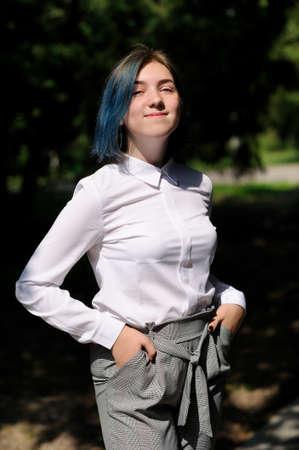 teenage girl in white blouse in green summer park