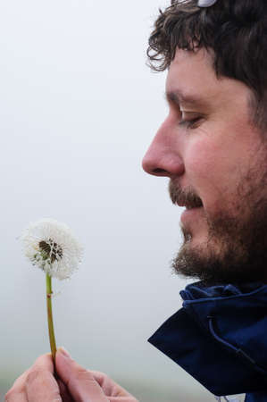 man holding dandelion with water drops in the hands and making a wish Stock Photo