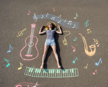 young girl laying on a asphalt with chalk drawn music theme, guitar and notes