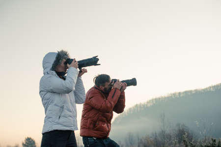 photographers with cameras outdoor making landscape pictures Stock Photo