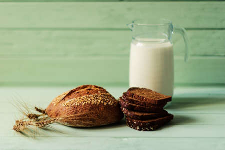 traditional bread loaf with spikelets and jug of milk on a lime wooden board