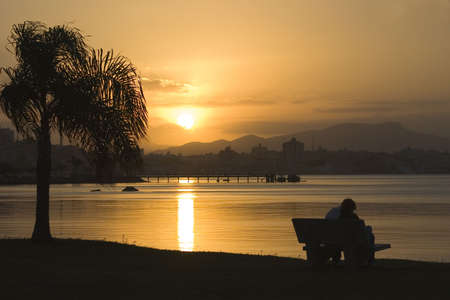 polis: A young couple contemplating the sunset on a tropical beach. Florianopolis - Brazil. Stock Photo