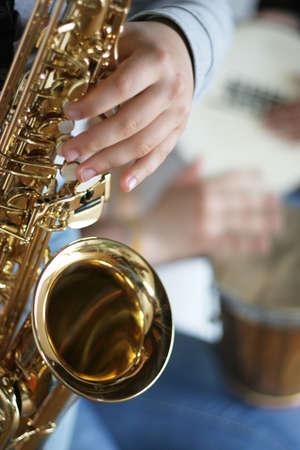 Sassofono giocatore con tamburi in background - concentrarsi sul dito del sassofonista
