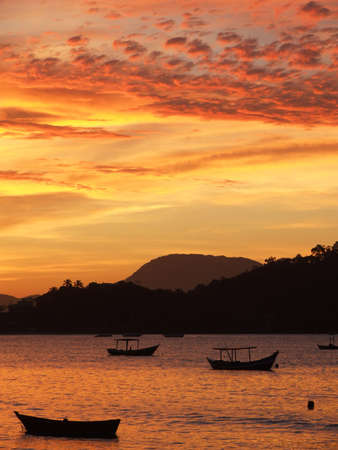 Sunset with fisherboats in the foreground in the bay of Porto Belo - Brazil.  Stock Photo