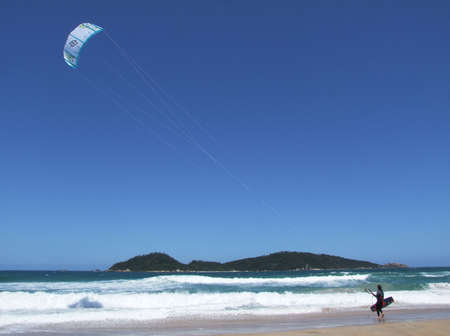 Kite surfer on the beach in Florianopolis with an island in the background