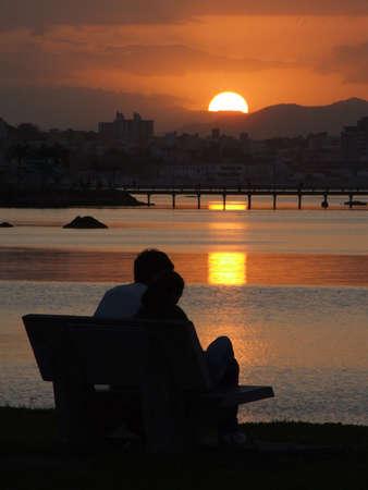 Pares jóvenes que comtemplan la puesta del sol en Florianopolis - Santa Catarina - el Brasil