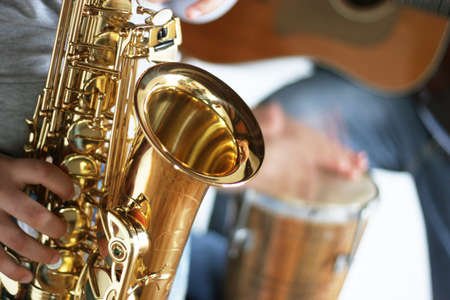 melodic: Closeup of a saxophone player with drums and guitar in the background - focus only on the part in the foreground of the saxophone Stock Photo