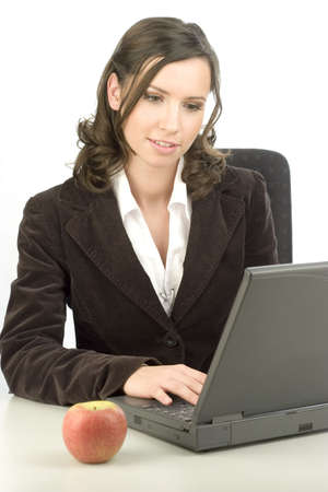Young woman typing on a laptop with an apple on the desk Stock Photo