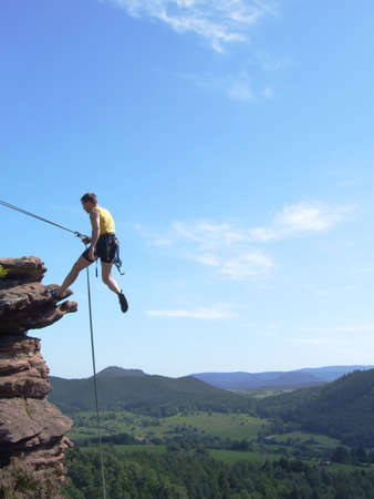 rappel: Free climber with rope against blue sky in Palatinate - Germany