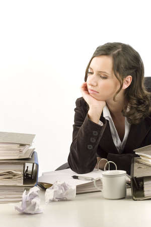 Stressed young woman sitting behind a desktop with folders and papers Stock Photo - 692307