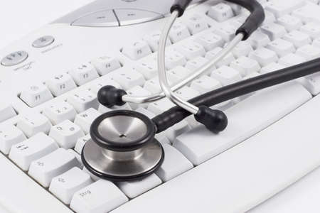 Stethoscope lying on a white keyboard on a white desk