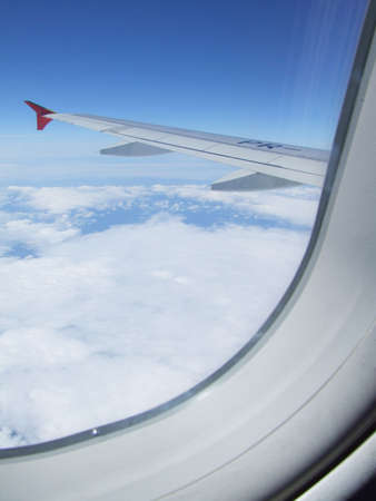 View from the window of an airplane on the wing and the clouds above