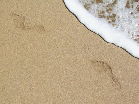 Female footprints on the beach with crestwaves coming from the side.