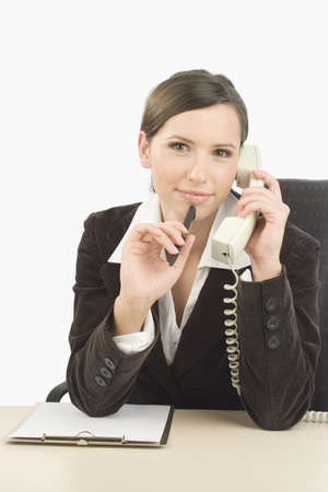 Young woman talking on the telephone with a ballpen in her hand Stock Photo - 705350