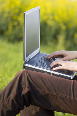 Woman working with a laptop on her knees outside in a meadow.