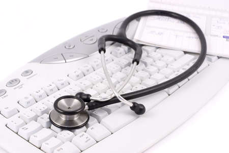 Stethoscope and medical record lying on a keyboard. Focus on the foreground.