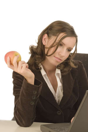 Young attractive woman looking at a laptop with an apple in her hand Stock Photo - 781476