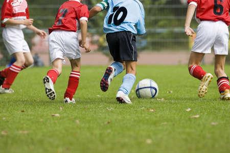 Detalle de un partido de fútbol con cuatro jugadores en acción