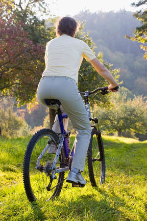 Woman on a mountainbike at sunset in autumn Stock Photo - 1728005