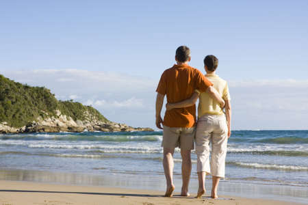 Couple walking arm in arm on a tropical beach Stock Photo - 2669810